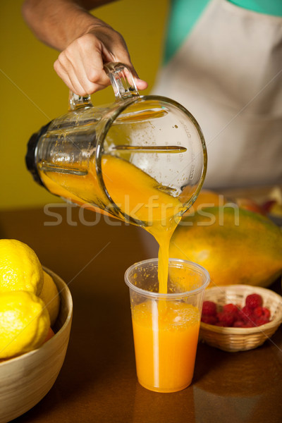 Female staff pouring juice into glass at counter Stock photo © wavebreak_media