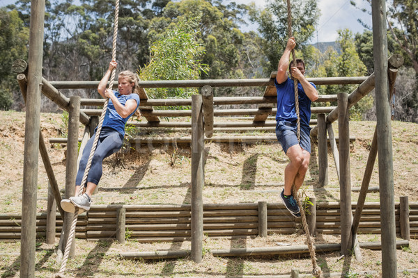 Fit man and woman climbing down the rope during obstacle course Stock photo © wavebreak_media