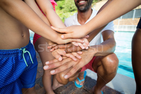 Male instructor and children stacking hands at poolside Stock photo © wavebreak_media