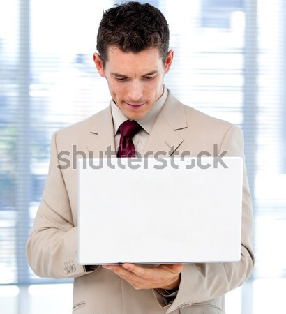 Concentrated businessman using a laptop standing Stock photo © wavebreak_media