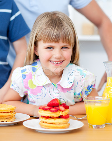 Portrait of a smiiling little girl eating waffles with strawberries Stock photo © wavebreak_media