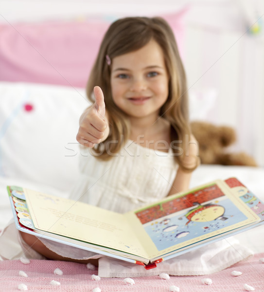 Little girl reading in bed with thumb up Stock photo © wavebreak_media