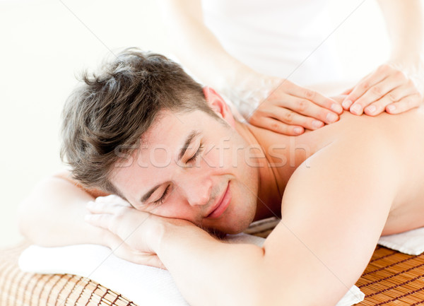 Relaxed young man receiving a back massage in a spa center Stock photo © wavebreak_media
