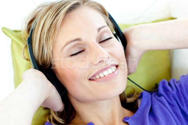 Bájos kaukázusi nő zenét hallgat fejhallgató kanapé Stock fotó © wavebreak_media