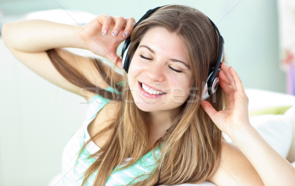 Encantado mulher ouvir música fones de ouvido sofá casa Foto stock © wavebreak_media