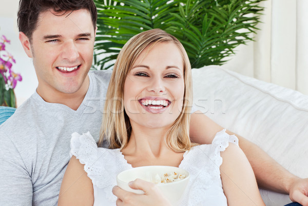 laughing couple eating pop-corn lying on the sofa in the living-room during the day Stock photo © wavebreak_media