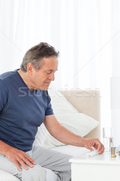 Sick man taking his pills at home Stock photo © wavebreak_media