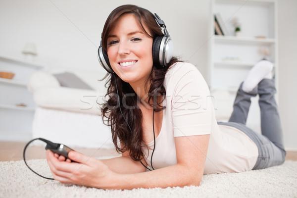 Bella bruna donna ascoltare musica lettore mp3 tappeto Foto d'archivio © wavebreak_media