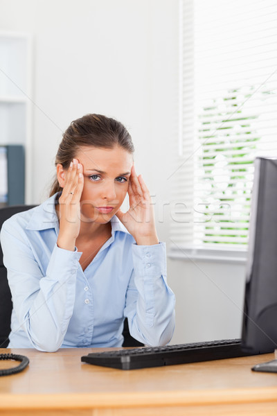 A stressed businesswoman is having a headache in an office Stock photo © wavebreak_media