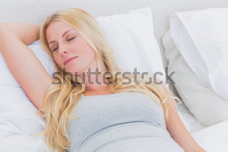Lovely woman yawning while sitting on her bed Stock photo © wavebreak_media