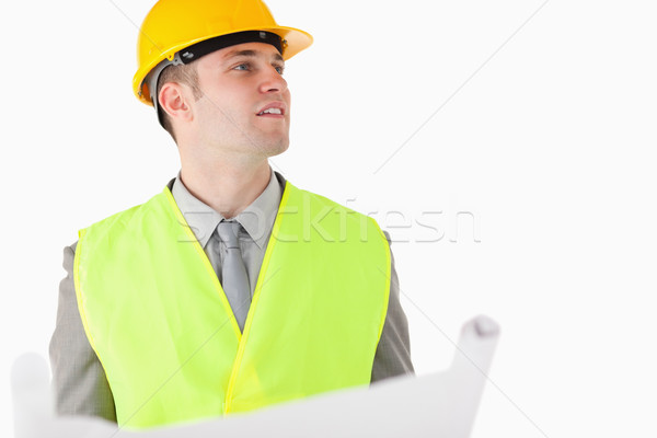 Builder holding a plan while looking around against a white background Stock photo © wavebreak_media