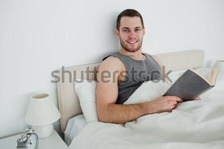 Man reading a novel while holding a cup of tea in his bedroom Stock photo © wavebreak_media