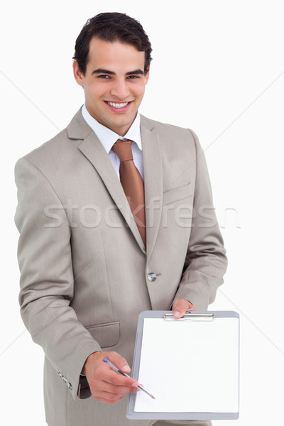 Smiling salesman asking for signature against a white background Stock photo © wavebreak_media