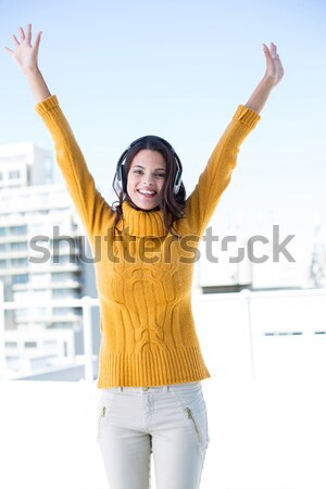 Smiling woman with arms risen against a white background Stock photo © wavebreak_media