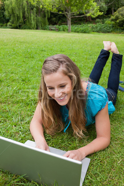 Smiling student typing on her laptop while lying down on the grass with legs raised Stock photo © wavebreak_media