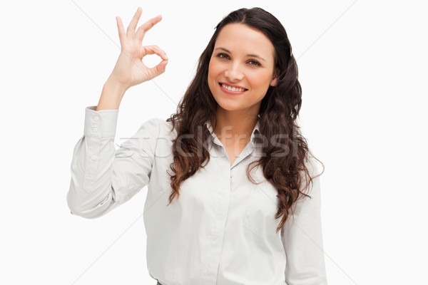 Portrait of a brunette approving with hand against white background  Stock photo © wavebreak_media