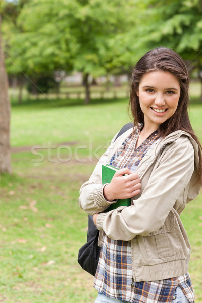 Portrait of a young smiling student holding textbook while posing in a park Stock photo © wavebreak_media