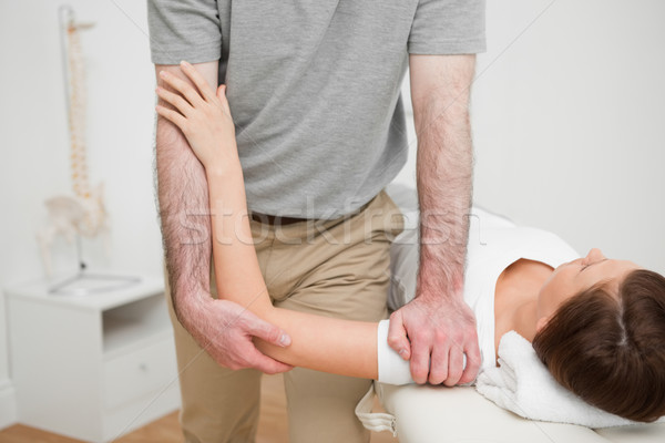 Physiotherapist pressing the shoulder of a woman in a medical room Stock photo © wavebreak_media