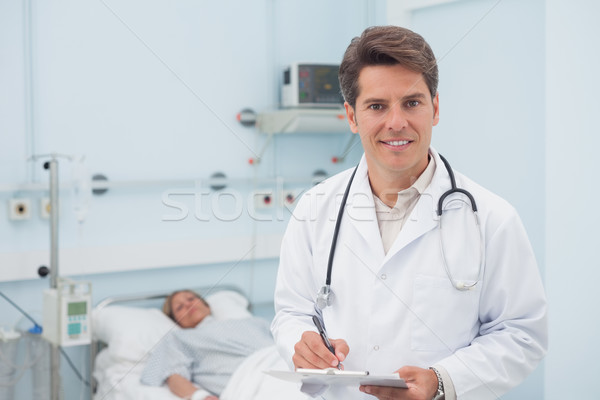 Doctor writing on a chart while smiling in hospital ward Stock photo © wavebreak_media