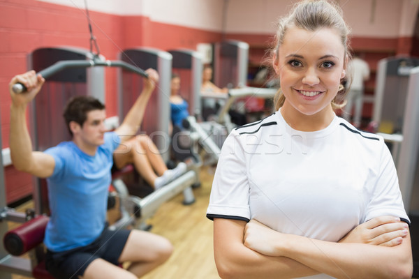 Female trainer smiling in front of class in weights room in gym Stock photo © wavebreak_media