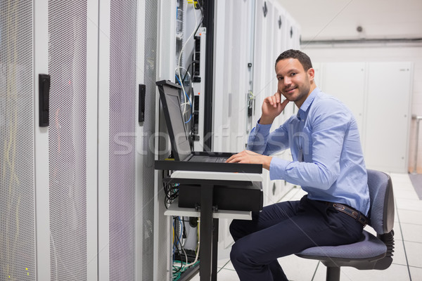 Smiling man looking up from working with servers in data center Stock photo © wavebreak_media