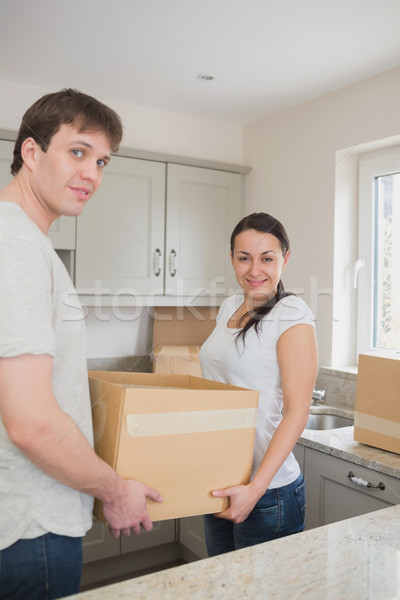 Young relocating couple standing in the kitchen while holding a box Stock photo © wavebreak_media