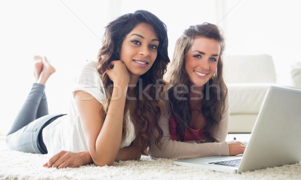 Twee glimlachend vrouwen typen computer vloer Stockfoto © wavebreak_media