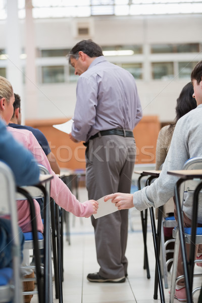 Students passing notes as teacher is talking to student in classroom Stock photo © wavebreak_media