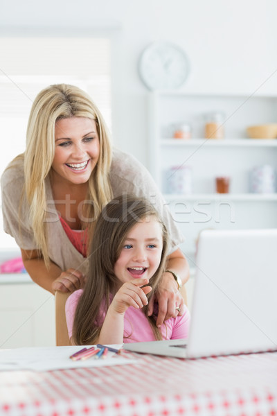 Stock photo: Mother and child laughing at laptop with child pointing in the kitchen
