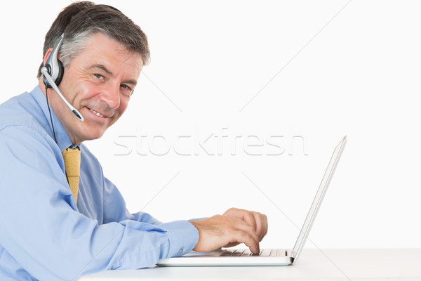 Smiling man with headphones typing on his laptop on his desk  Stock photo © wavebreak_media