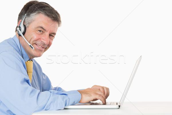 Sorridere uomo cuffie digitando laptop desk Foto d'archivio © wavebreak_media
