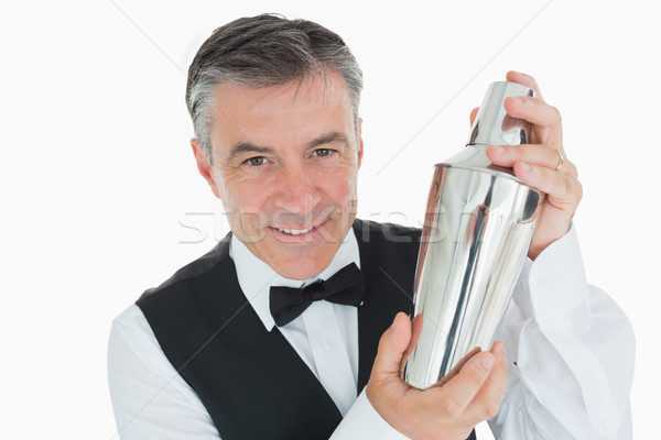 Smiling waiter in suit shaking drink in cocktail shaker Stock photo © wavebreak_media