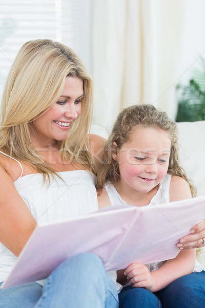Smiling mother and daughter sitting on the sofa with a book Stock photo © wavebreak_media