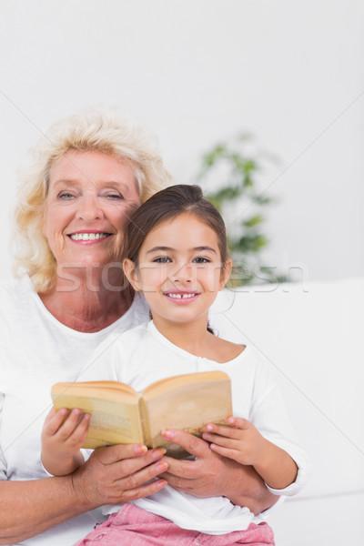 Smiling granddaughter and grandmother reading a novel together Stock photo © wavebreak_media