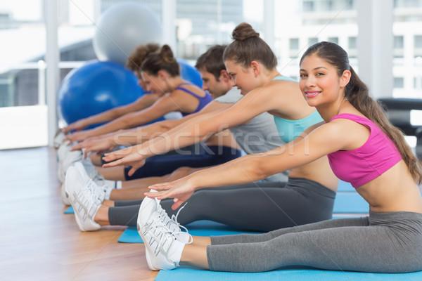 Sporty people stretching hands to legs in fitness studio Stock photo © wavebreak_media