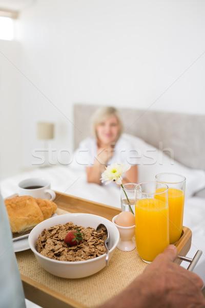 Kobieta posiedzenia bed śniadanie pierwszy plan szczęśliwy Zdjęcia stock © wavebreak_media