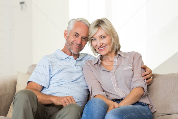 Smiling mature couple sitting on sofa with arm around Stock photo © wavebreak_media