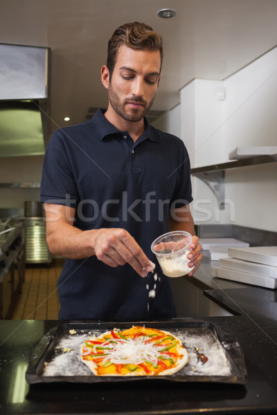 Pizza chef sprinkling cheese over pizza Stock photo © wavebreak_media