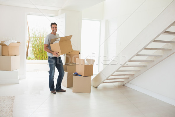 Stock photo: Smiling man carrying boxes in a new house