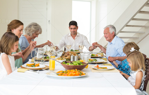 Family praying together before meal at dining table Stock photo © wavebreak_media