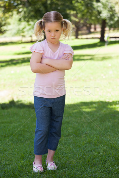 Stock photo: Portrait of a sad girl with arms crossed at park
