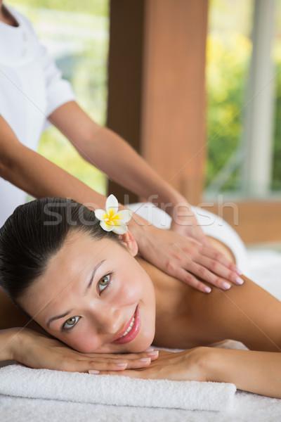 Brunette enjoying a peaceful massage smiling at camera Stock photo © wavebreak_media