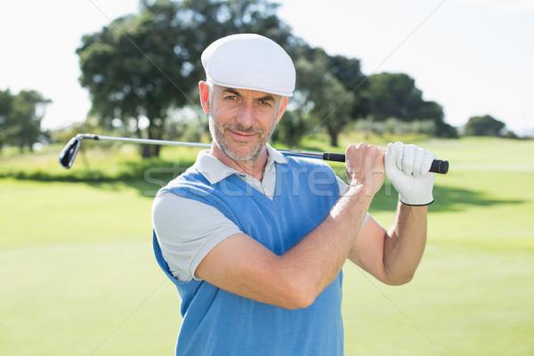 Golfer standing and swinging his club smiling at camera Stock photo © wavebreak_media