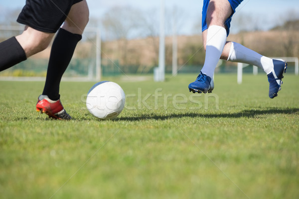 Football players tackling for the ball on pitch Stock photo © wavebreak_media