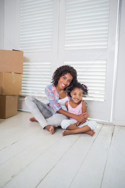 Mother and daughter sitting on the floor smiling at camera Stock photo © wavebreak_media