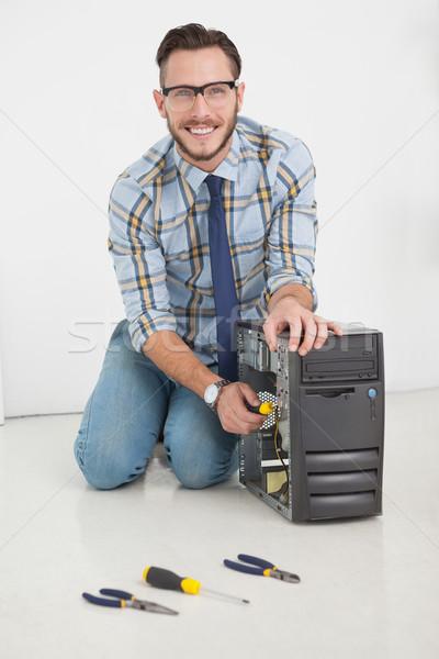 Computer engineer working on broken console with screwdriver Stock photo © wavebreak_media