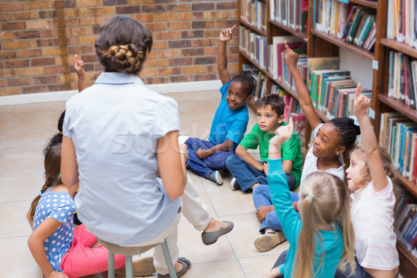 Cute pupils and teacher having class in library Stock photo © wavebreak_media