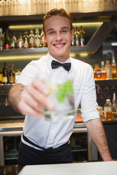 Happy bartender offering cocktail to camera Stock photo © wavebreak_media
