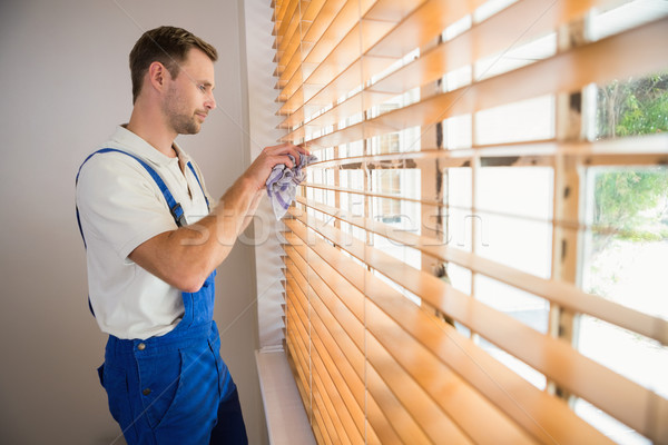 Stock photo: Handyman cleaning blinds with a towel