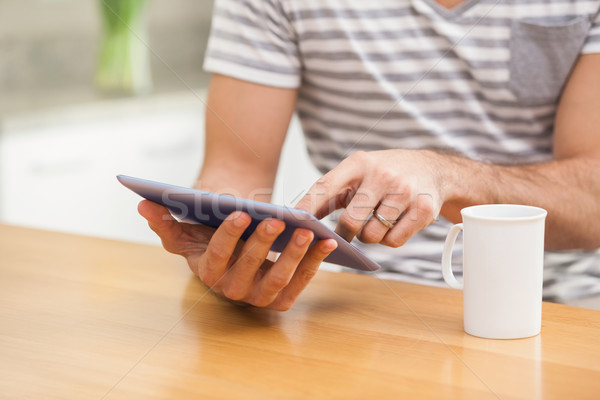 Young man using tablet while having coffee Stock photo © wavebreak_media